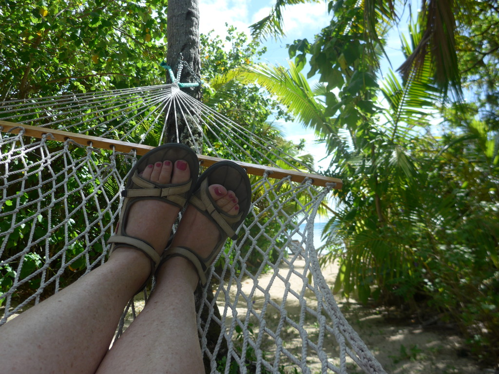 Sūsana relaxing in the hammock with the beach just through the trees.